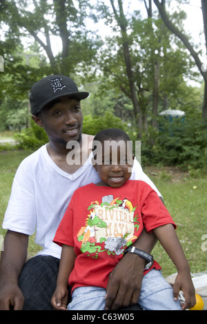 Portrait of a young man with child who works with a childcare center in inner city Detroit. - Stock Photo