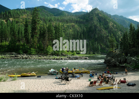 Rubber paddle boats, dory and inflatable kayaks with the O.A.R.S. group camping at sandy beach on Main Salmon River - Stock Photo