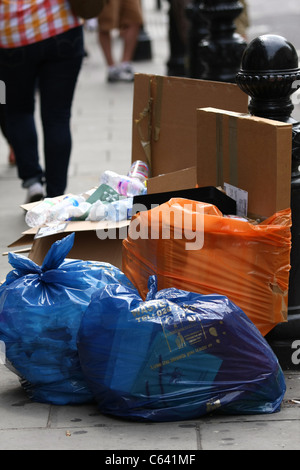 Bags of rubbish on a kerbside in London - Stock Photo
