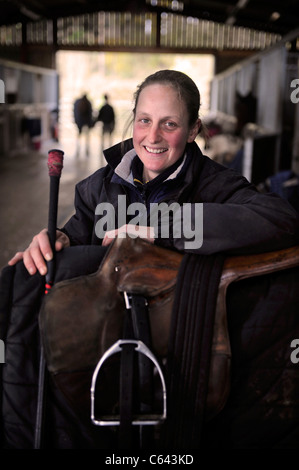 A female jockey with a racehorse at a stable in Gloucestershire UK - Stock Photo