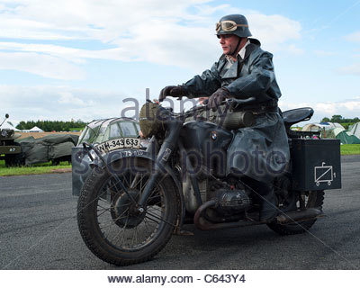 A man dressed as a world war ii German soldier riding a motor bike, at a re enactment and nostalgia weekend at Croft - Stock Photo