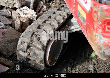 Detail of rubber padded continuous or caterpillar track on small digger machine - Stock Photo