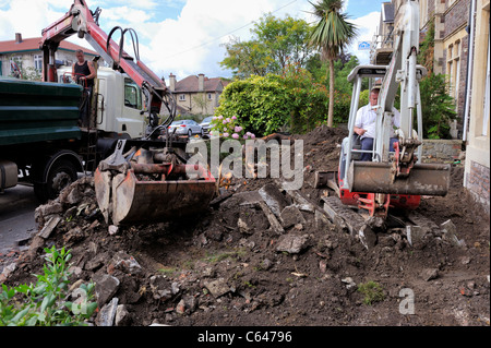 Mechanical excavators clearing residential garden for paving - Stock Photo