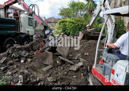 Mechanical excavators clearing ground residential garden - Stock Photo