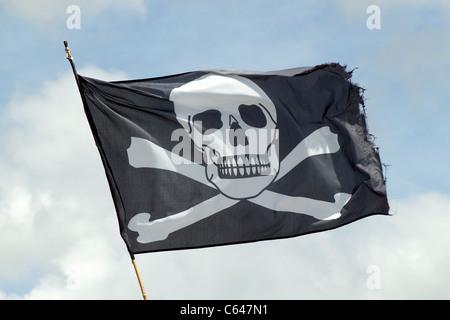 The Jolly Roger pirates ship skull and crossbones flag. - Stock Photo