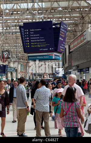 travelers under the direction sign board in Waterloo Station - Stock Photo