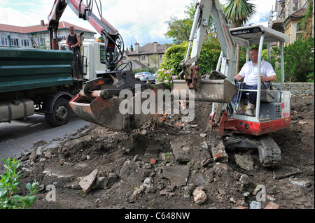 Mechanical excavators ground clearance of residential garden - Stock Photo