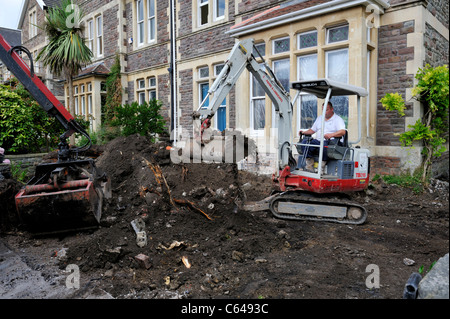 Mechanical mini digger and bucket scoop clearing ground of residential garden - Stock Photo