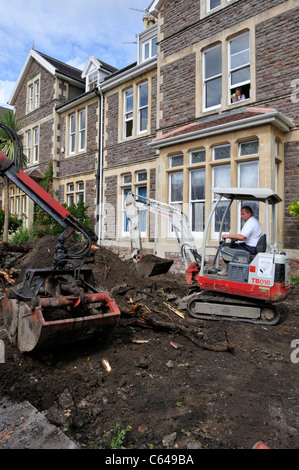 Mini digger and bucket scoop crane doing ground clearance of residential garden. Preparation for paving. - Stock Photo