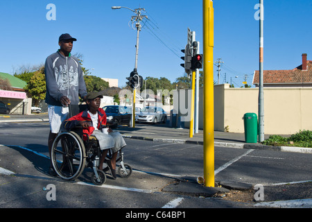 Boy in a wheelchair is assisted to cross a road in Cape Town South Africa - Stock Photo