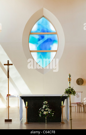 Altar and stained glass window in modern church - Stock Photo