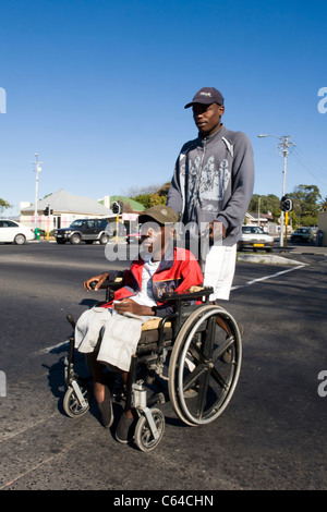 Boy in a wheelchair is assisted by a carer to cross a road in Cape Town South Africa - Stock Photo