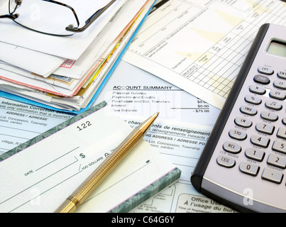 A pile of bills, checkbook, pen and calculator on the table.