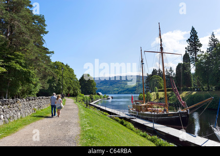 Couple walking along the banks of the Caledonian Canal towards Loch Ness, Fort Augustus, Highland, Scotland, UK - Stock Photo