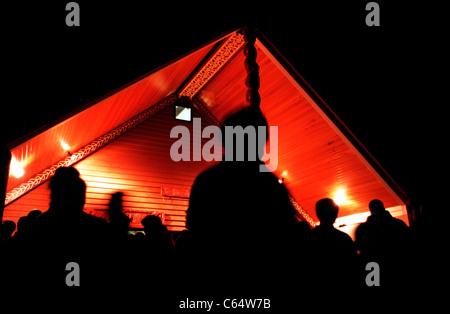 A Maori marae with Maori people at night. - Stock Photo