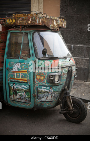 Traditional painting on Vintage three wheels Vespa moped parked near the market, Sicily - Mediterranean coast, Italy, - Stock Photo