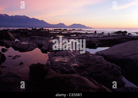 Beautiful landscape photo of Kaikoura rock pools and beach at sunset - Stock Photo