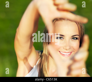 Pretty girl having fun outdoor, making frame with hands, taking picture with imaginary camera, selective focus - Stock Photo