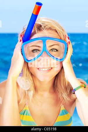 Funny portrait of a beautiful young girl with an underwater mask on the beach, vacation and summertime outdoor fun - Stock Photo