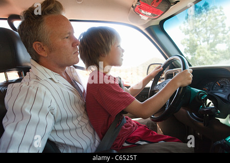 Boy sitting on man's lap driving car - Stock Photo