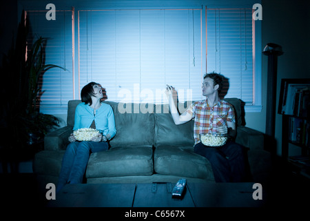 Young couple throwing popcorn and catching it in mouth - Stock Photo