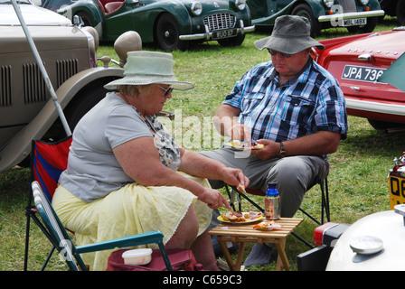 couple having a picnic at classic car meeting  United Kingdom - Stock Photo