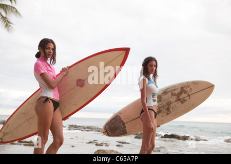 Two young women holding surfboards, portrait - Stock Photo