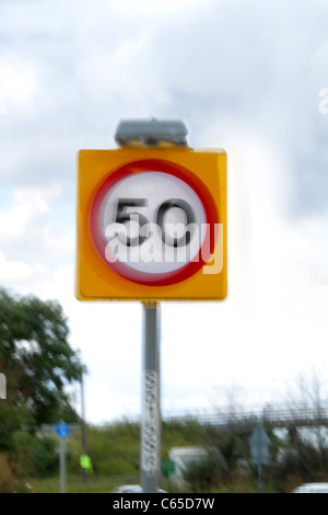 A 50 mph British speed limit sign showing movement to indicate excess speed - Stock Photo