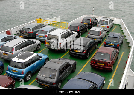 Vehicles on deck of car ferry with sea background. UK - Stock Photo