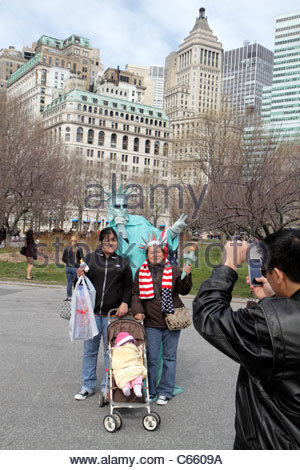 Lower Manhattan New York City NYC NY Battery Park street performer busker mime living statue Statue of Liberty Asian - Stock Photo