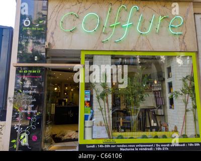 A neon sign outside a beauty salon indicating they do hair for Hair salon paris france