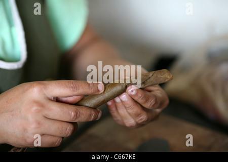 A man hand-rolling a puro (cigar), at the Doña Elba brand on Calle la Libertad. Granada, Nicaragua, Central America - Stock Photo