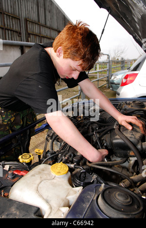 Youth learning car mechanic skills at an initiative to foster teamwork and confidence skills amongst disadvantaged - Stock Photo