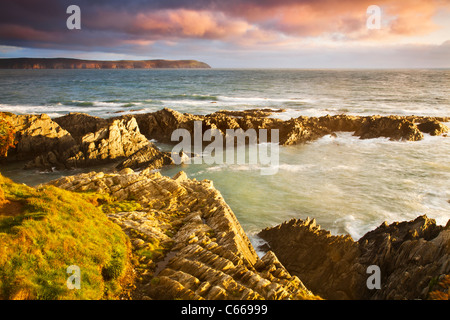 Evening light falls on the rocks of Barricane Beach, Woolacombe,looking towards Baggy Point, North Devon, England, - Stock Photo