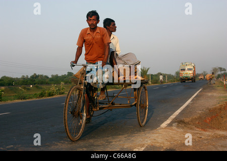 Indian pedal tricycle at sunset carrying cargo and passenger up a highway in West Bengal India - Stock Photo