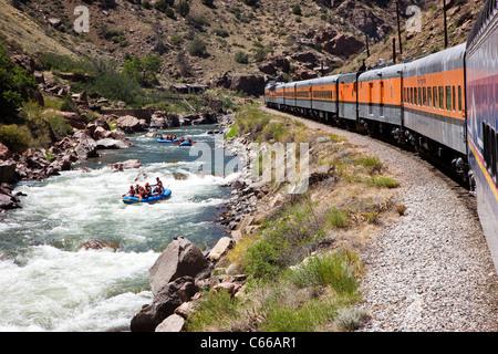 Popular tourist train runs through the 1,000' deep Royal Gorge Route along the Arkansas River, Colorado, USA - Stock Photo