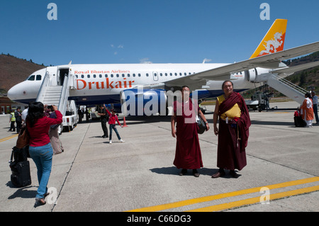 Two monks and tourists in front of Drukair plane at Paro airport. Bhutan - Stock Photo