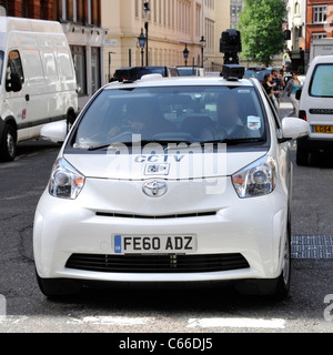Roof mounted camera on white CCTV surveillance car with driver assistant working & driving along in London West - Stock Photo