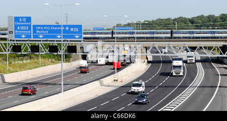 Railway bridge and train crossing Junction 28 of the M25 UK motorway with signs - Stock Photo