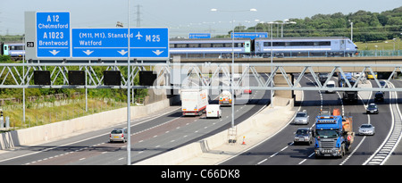 Transport concept choices passenger train on railway bridge crossing road traffic Junction 28 of the M25 motorway - Stock Photo
