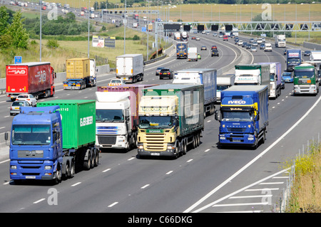 Transport lorry truck four lanes section of M25 motorway Essex countryside overtaking slower hgv lorries & trucks - Stock Photo