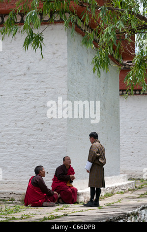 2 monks and man in gho talking at chorten. Paro. Bhutan - Stock Photo