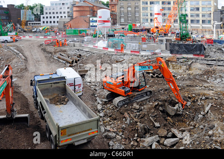 Digger loads tipper lorry at new Crossrail train station construction site above existing Tottenham Court Road tube - Stock Photo