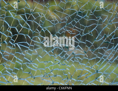 A view through a broken window on a pastel green background - Stock Photo
