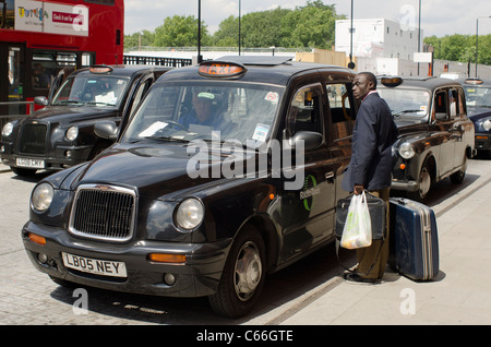 Gentleman waiting outside a Black Cab in London, England. - Stock Photo