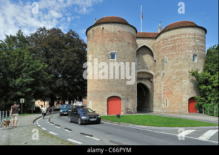 Traffic leaving town and the city gate Gentpoort / Ghent Gate in Bruges, Belgium - Stock Photo
