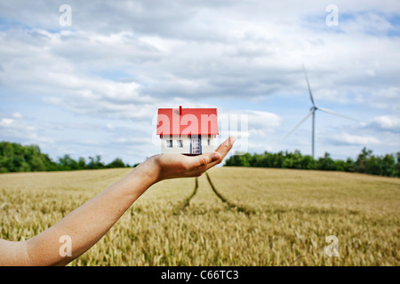 Woman with model house at wind turbines - Stock Photo