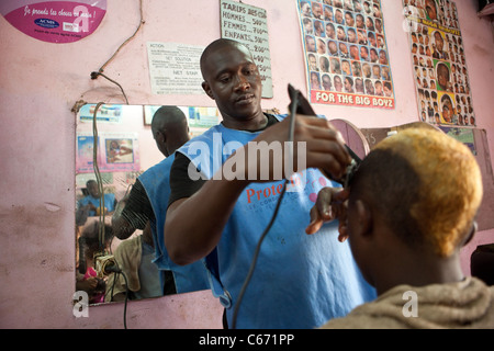 A barber cuts hair in Yaounde, Cameroon, West Africa. - Stock Photo