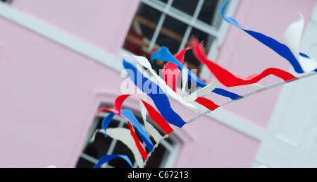 Bunting hanging in a street in the Cornish town of Fowey, Cornwall, England. - Stock Photo