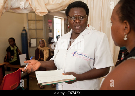 A nurse consults with a patient at a clinic in Kampala, Uganda, East Africa - Stock Photo